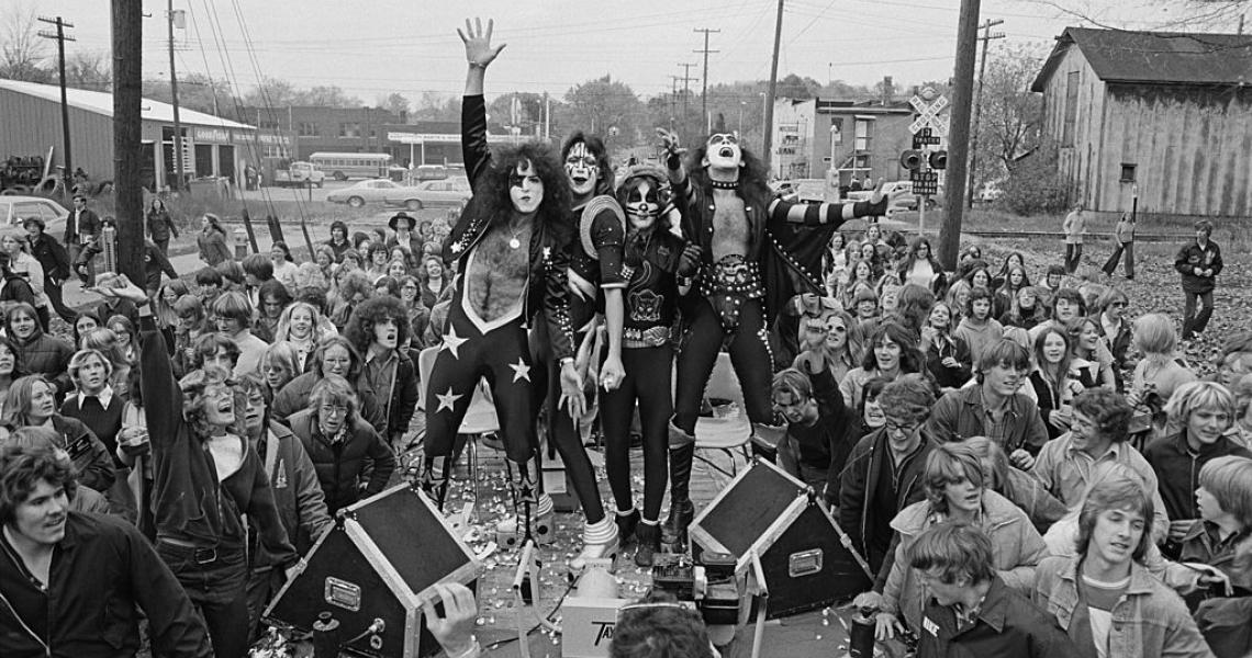 "CADILLAC, MICHIGAN - 9th OCTOBER: Photo of Paul STANLEY and Gene SIMMONS and KISS; Paul Stanley and Gene Simmons, posed on podium in front of crowd of people from town. ""Day in the Life of Town"" in Cadillac, Michigan on 9th October 1975. (Photo by Fin Costello/Redferns)"